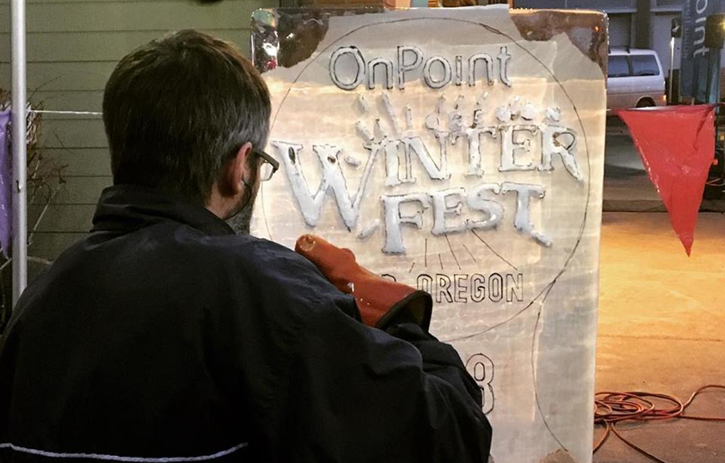 Man works on ice sculpture at First Friday event in celebration of the upcoming WinterFest event