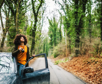 Young woman exploring the woods from her car