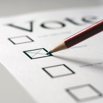 A voting card marked with an x in the second box with a pencil. The focus is on the pencil tip.