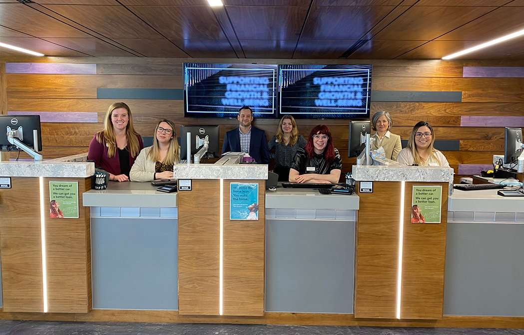 Interior of Lombard branch with employees lined up behind the teller row, celebrating the new North Lombard Branch.