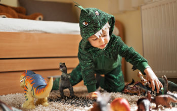 toddler boy in a dinosaur costume playing with his dinosaurs figures in his playroom