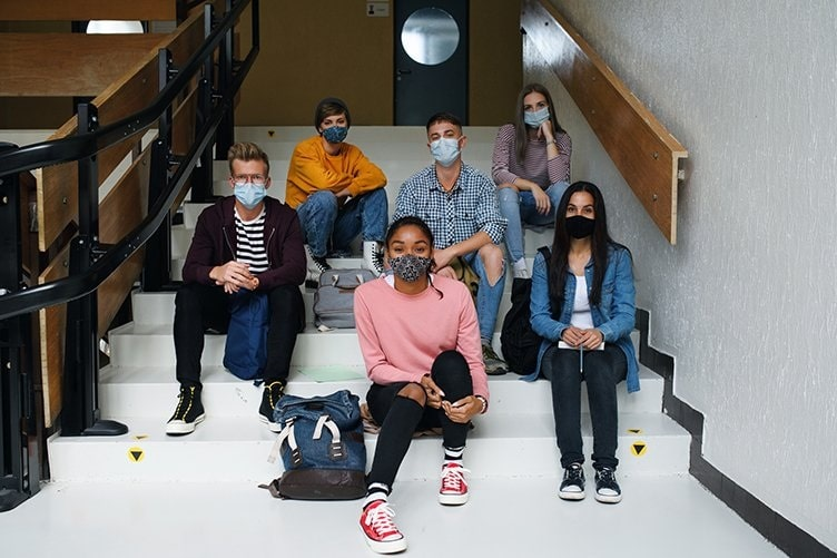 Building upon our educational roots to foster success in our community_diverse group of students sitting on stairs at school while wearing masks