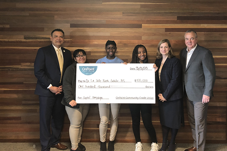OnPoint presents display check of $100,000 to officials and students of De La Salle North Catholic High School