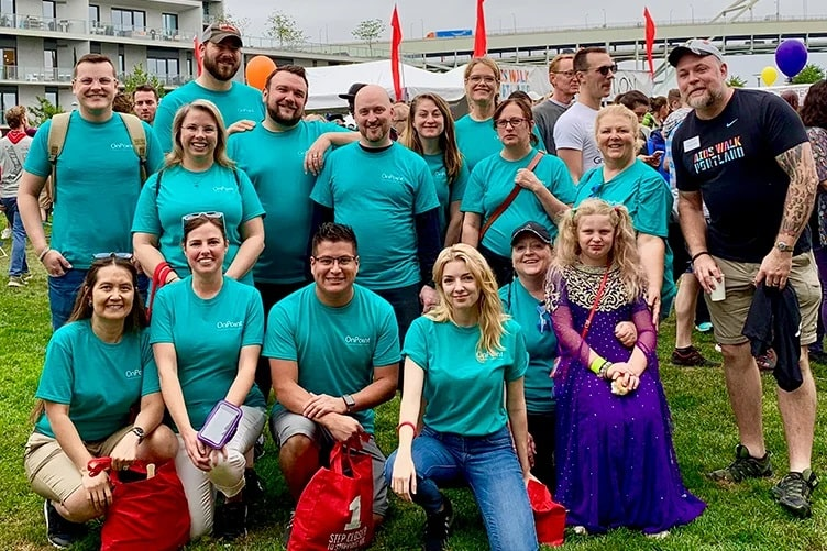Group of OnPoint employees in their volunteer t-shirts pose at the end of volunteering at the Portland AIDS Walk.