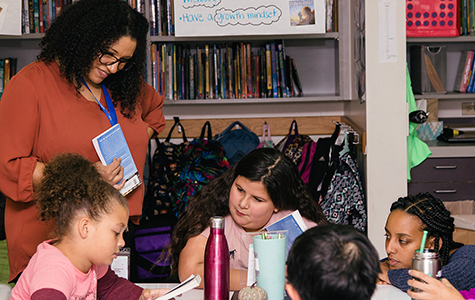 Teacher reviews book with a small group of students in the classroom in Gilbert Heights Elementary