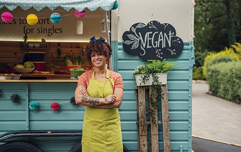 Proud small business owner stands in front of her vegan food cart with her arms folded.
