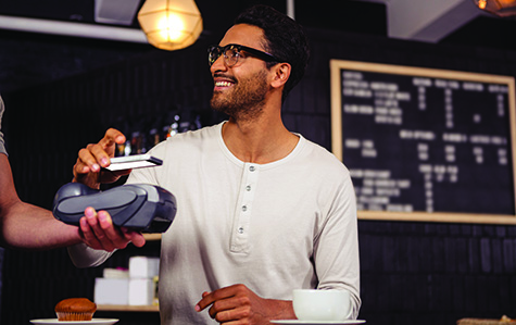 Man in glasses hovering phone over payment terminal smiling as he makes a purchase
