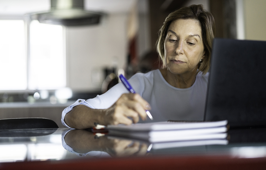 Mature woman writing on a notepad in front of her computer while attending a webinar