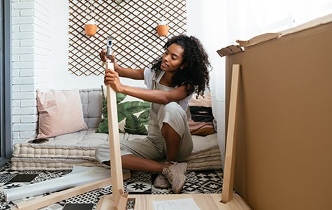 Woman in her new home putting together a small table