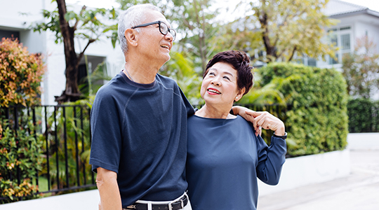 Happy retired senior Asian couple walking and looking at each other with romance in outdoor park and house in background