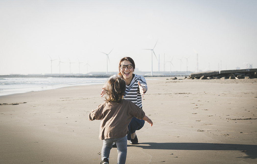Mother and child playing in the beach where there is wind power station in the background.