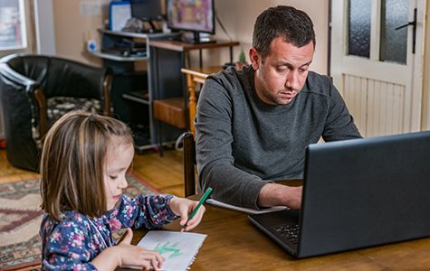 Father working from home with young child in quarantine isolation