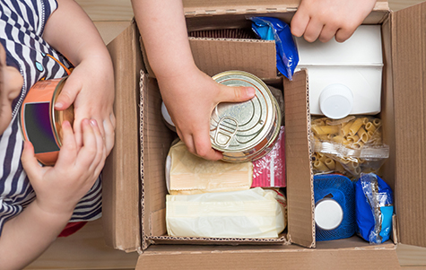 Children opening a food delivery box at home, online ordering. Grocery store delivery. Box full of food in concept donation boxparcel. Delivery during quarantine due to coronavirus COVID-19 disease