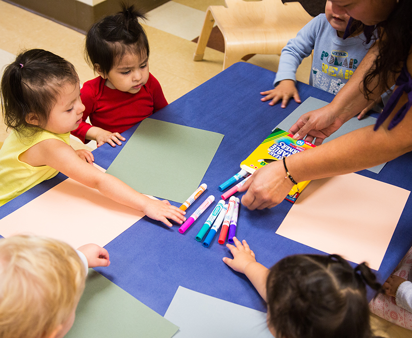 OnPoint Employees Direct $91,000 to Local Non-profits_pre-school children around a table being helped to markers to start an art project