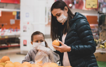Young woman with child girl in medical masks buys a oranges at supermarket
