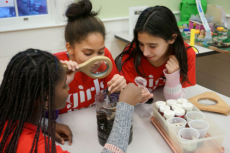 Young girls work on a science experiment as part of the Girls Inc program.