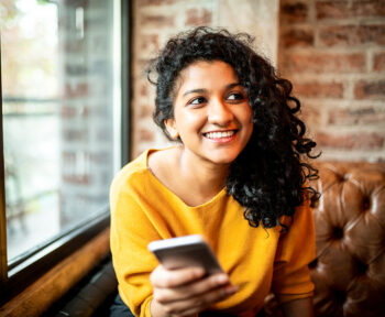 Woman smiling looking at someone off camera while holding her mobile phone.