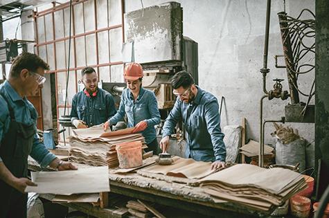 Team Of Carpenters Gluing Wooden Parts Together In Workshop