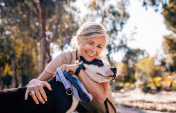 Affectionate mature woman embracing pet dog in nature