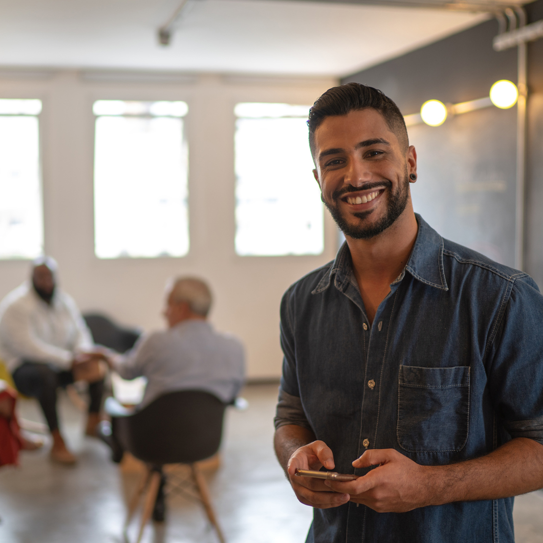 Teach employees about cybersecurity_How Small Business Owners Can Teach Their Employees About Cybersecurity_Young Man holding cell phone with coworkers in background