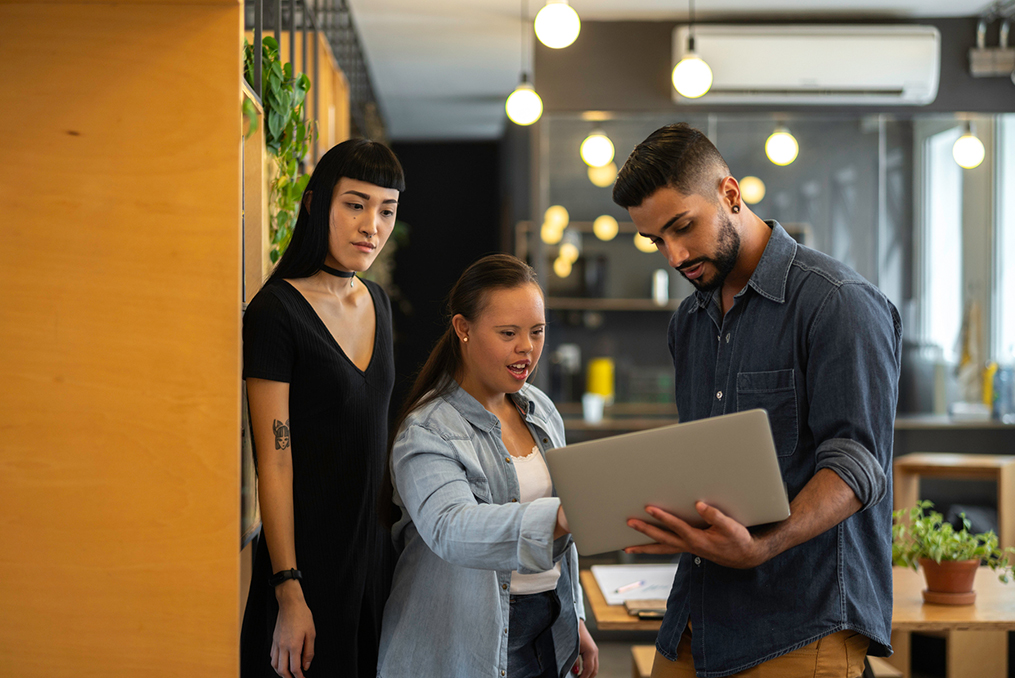 Teach employees about cybersecurity_How Small Business Owners Can Teach Their Employees About Cybersecurity_Young Man holding laptop teaching coworkers