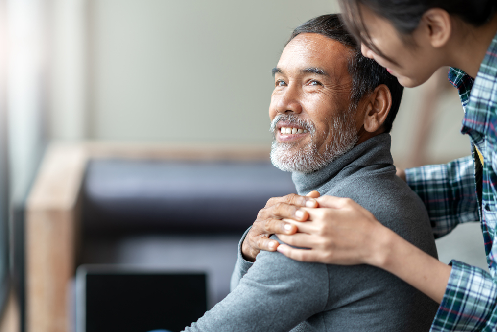 Smiling happy older asian father touching daughter's hand on shoulder looking and talking together with love and care