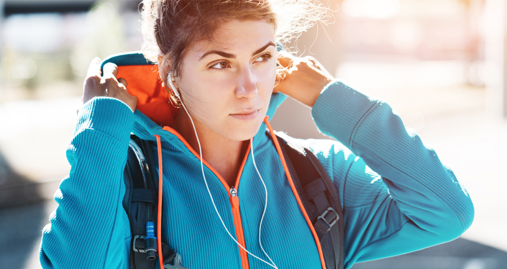 7 Ways You May Be Hurting Your Credit_Woman with backpack putting on her hood and contemplating
