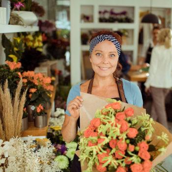 Flower Shop Owner Hero shot showcasing bouquet of flowers in her shop