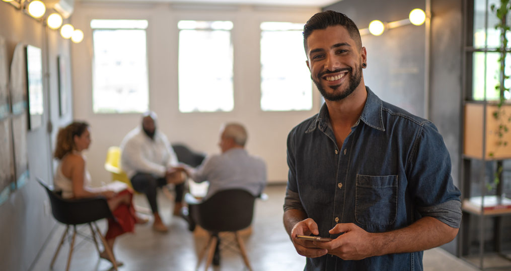 How Small Business Owners Can Teach Their Employees About Cybersecurity_Young Man holding cell phone with coworkers in background
