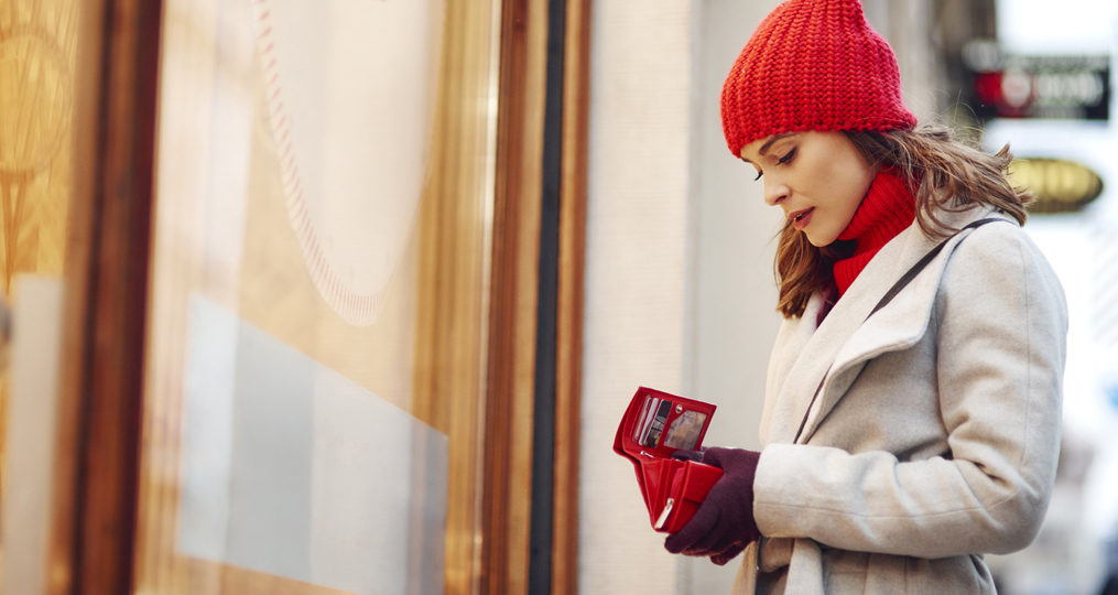 How to Prevent the Holiday Financial Crunch_Woman standing outside a storefront looking concerned