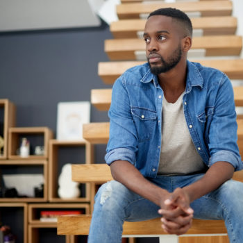 Managing Student Loan Debt during COVID-19_Concerned young man sitting on steps