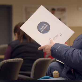Woman holding a wealth management and investment services folder while attending a PERS seminar