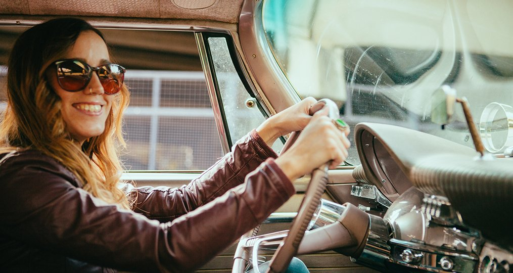 Smiling Young Woman Driving Vintage American Car_6_step_plan_for_getting_your_finances_in_order_taking_control_vintage_car