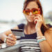 Vishing How to Protect Yourself From Phone Fraud_Woman holding her credit-debit card while talking on the phone