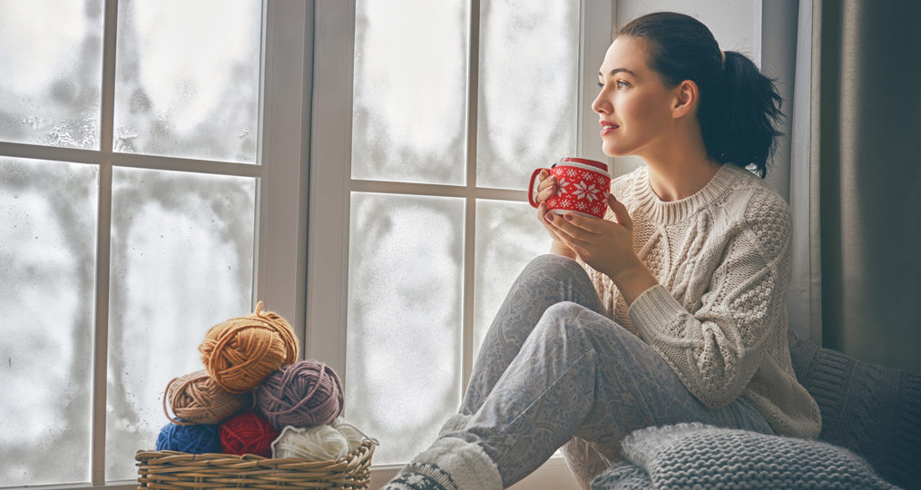 What Is a Credit Freeze and Should You Freeze Your Credit_woman sitting near her window looking out at the winter cold