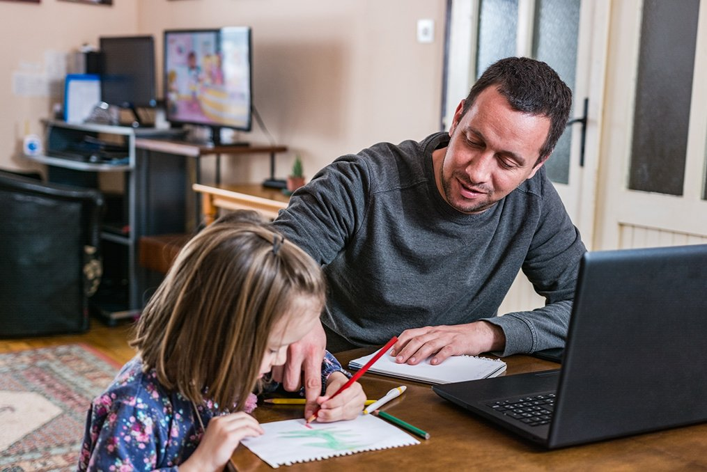 5 Steps to Take If You Lost Your Job in Oregon State_Man slooking for a job from home while helping his daughter with schoolwork