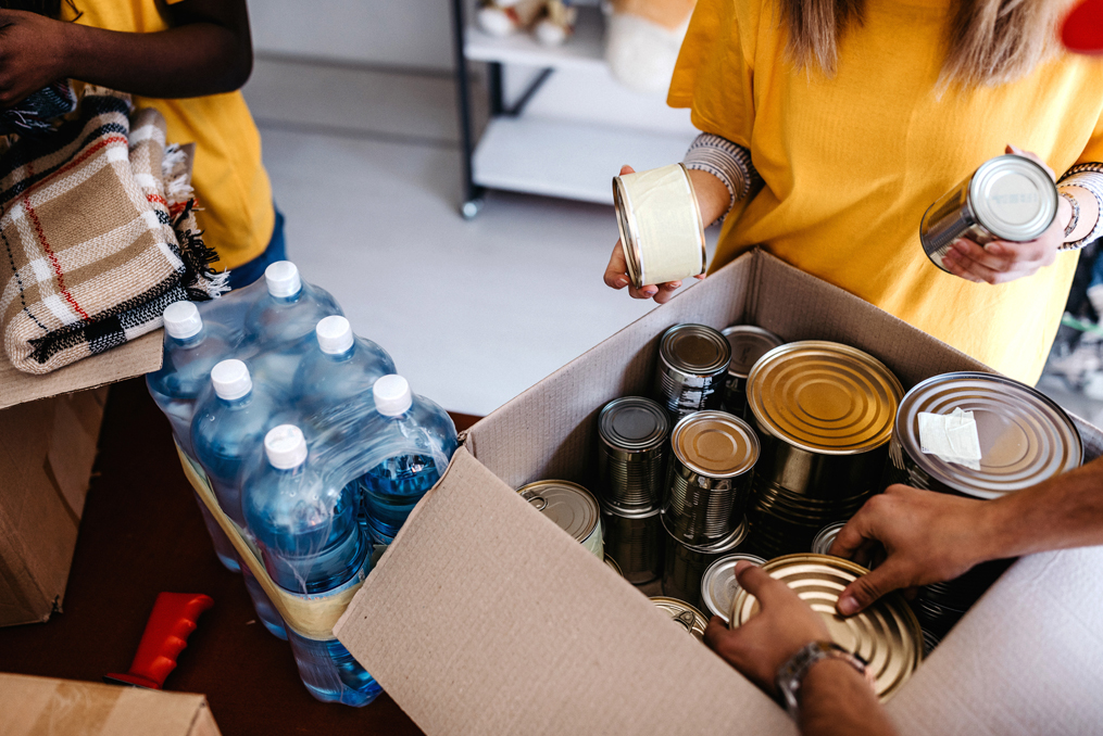Don't Get Scammed by a Fake Charity This Giving Season_workers placing food donations into box