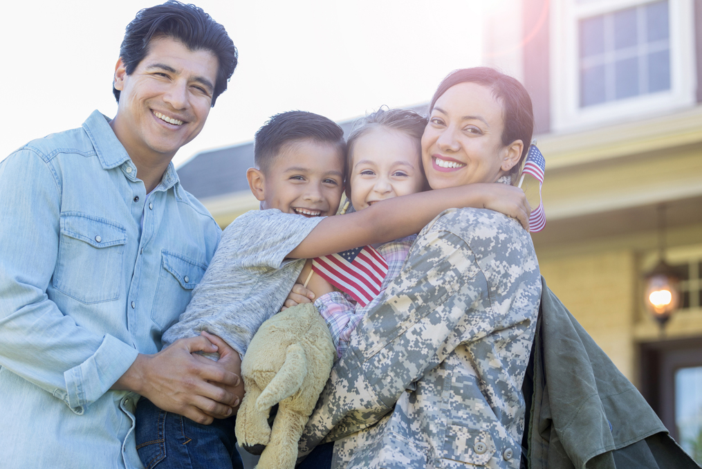 Servicemembers Are You Using All of Your Military Benefits_Military Member with family outside her house