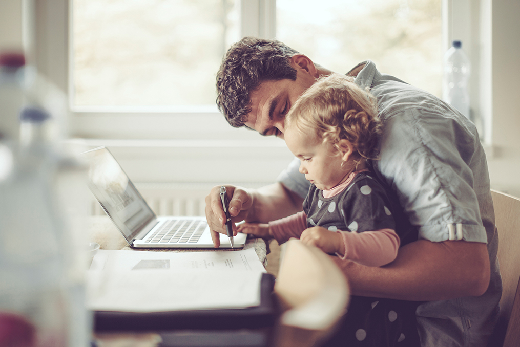 Strategies for Quitting the Paycheck-To-Paycheck Life_Father and child sitting at table working on documents