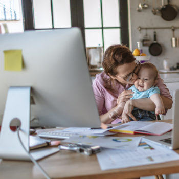 mom kissing baby while sitting at the dining table doing finances
