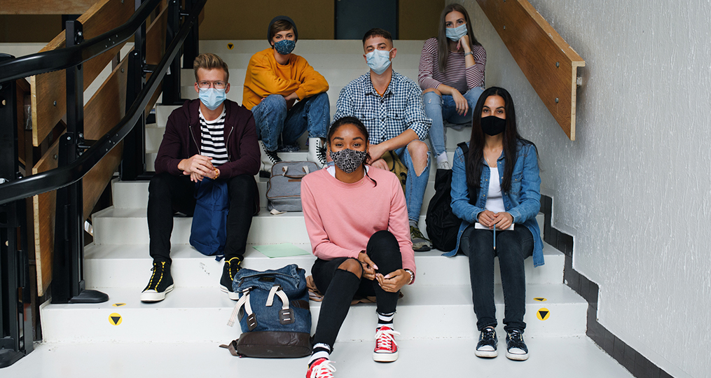 Building upon our educational roots to foster success in our community-diverse group of students sitting on stairs at school while wearing masks