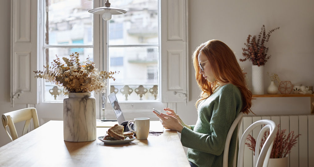 10 Steps to Take If Your Personal Information Is Stolen_woman researching her personal accounts in her kitchen