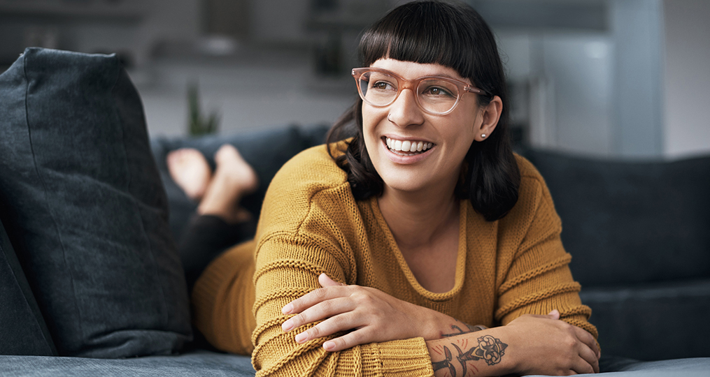 4 smart ways to use your tax refund_woman smiling and thinking on her couch