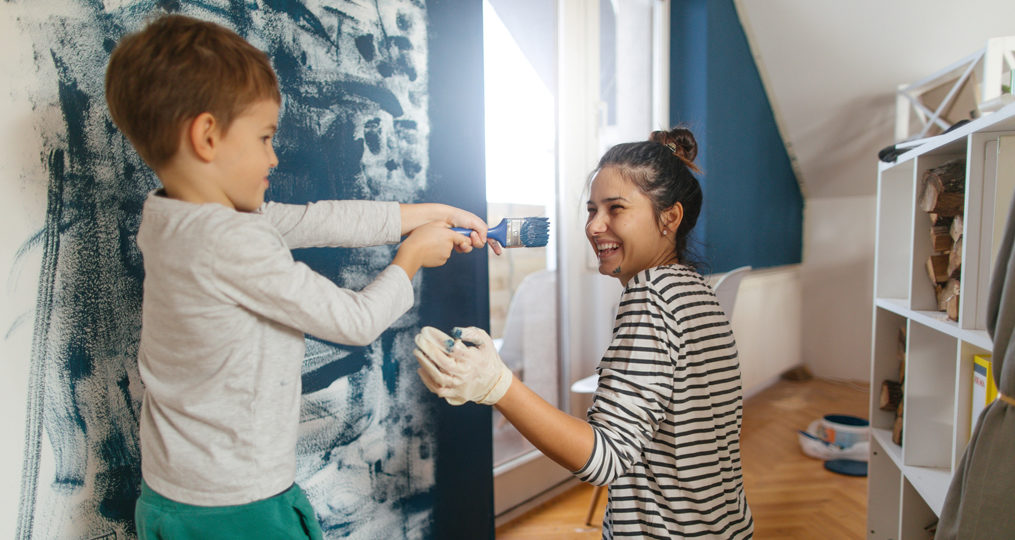 5 ways to finance home improvement projects_mother and son having fun while painting a bedroom wall