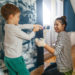 mom and son having fun while painting a bedroom wall