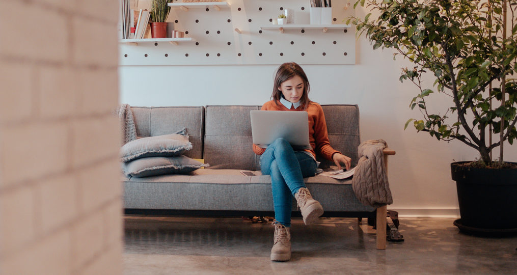 Common Personal Finance Rules and What They Mean_Young woman sitting on her couch with her laptop