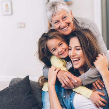 Financial Literacy Lessons for All Ages_Multi generational family sitting on couch hugging and laughing