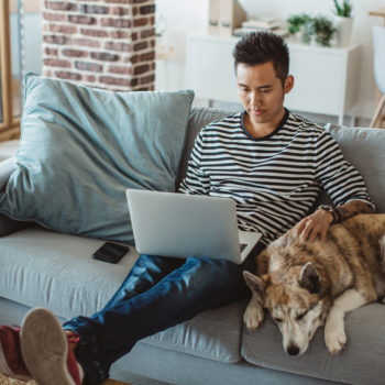 Financial Planning Resources for Home-Bound College Students_young man sitting on his couch with his dog looking at his laptop