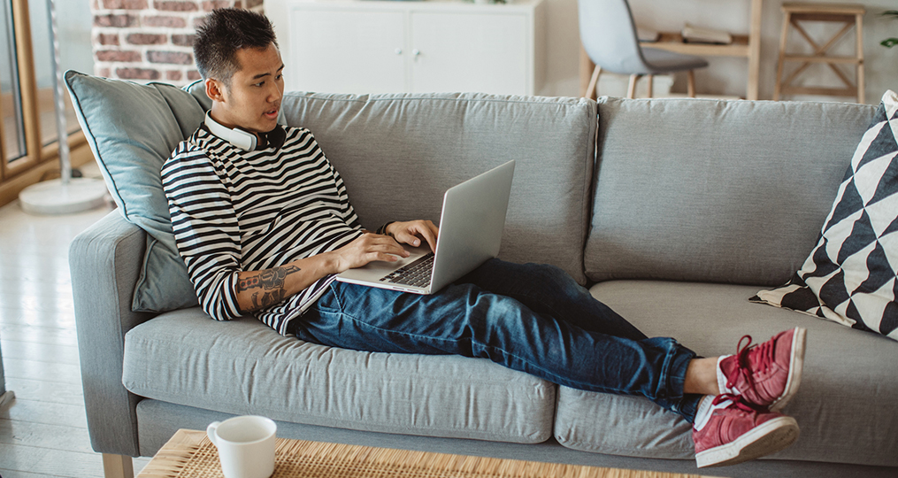 Financial Planning Resources for Home-Bound College Students_young man sitting on his couch with his laptop