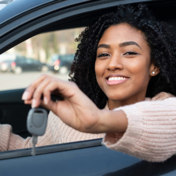 How to Spot Red Flags When Buying and Selling Vehicles_young woman holding the keys to her new car